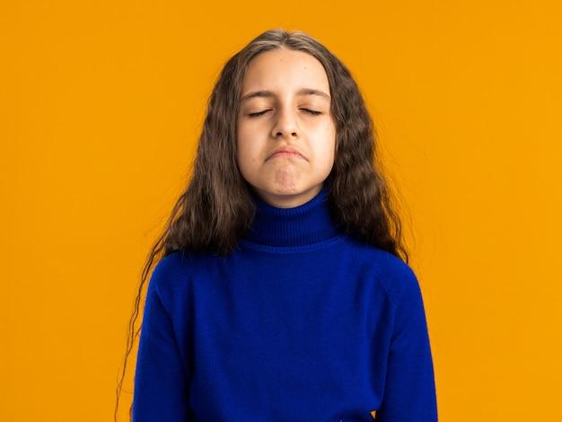 Trauriges teenager-mädchen mit geschlossenen augen isoliert auf orangefarbener wand