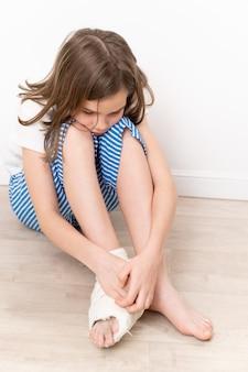 Trauriges teenager-mädchen mit orthopädischem pflaster am fuß auf dem boden sitzend.