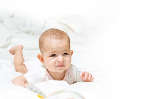 Trauriges und enttäuschtes baby liegt auf dem bett säuglingskind auf dem bauch sabbern und zahnen