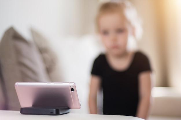 Trauriges und müdes kleines mädchen, das zu hause vor dem smartphone studiert. fernunterricht, online-unterricht für kinder. computersucht von kindern, kindersicherung.