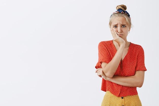 Trauriges und unruhiges junges blondes mädchen, das gegen die weiße wand aufwirft