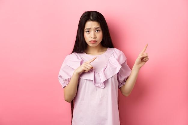 Trauriges und verzweifeltes asiatisches mädchen runzelte die stirn, schmollte und zeigte mit den fingern direkt auf enttäuschende schlechte nachrichten, fühlte sich unglücklich und stand vor rosa hintergrund.