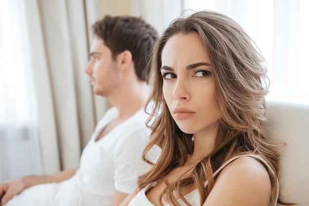 Trauriges unglückliches junges paar, das probleme im bett hat