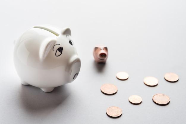Trauriges unglückliches sparschwein des weißen porzellans und euro-münzen