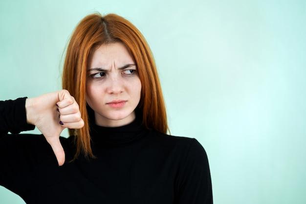 Trauriges unzufriedenes rothaariges mädchen, das daumen unten zeichen mit ihren fingern zeigt.