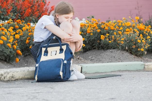 Trauriges, verzweifeltes junges mädchen, das unter mobbing und belästigung leidet und einsam, unglücklich verzweifelt und hoffnungslos im freien sitzt. schulisolation, missbrauch und mobbingkonzept