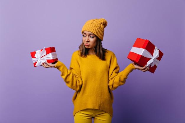 Trauriges wunderschönes mädchen im gelben hut, der geburtstagsgeschenke hält. innenporträt der emotionalen brünetten dame, die nach neujahrsparty aufwirft.