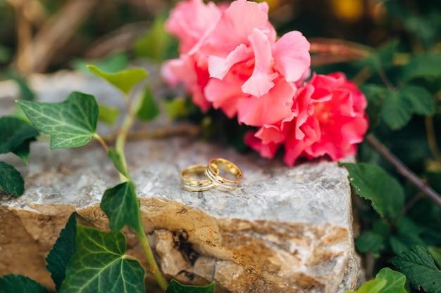 Trauringe auf den steinen im gras-efeu- und oleander-zweig
