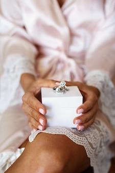 Trauringe aus weißgold und diamanten liegen auf weißem kasten in den armen der braut