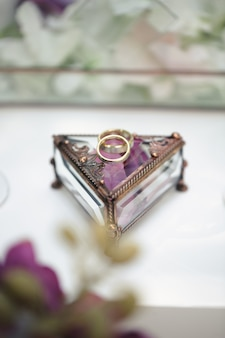 Trauringe in einer glasbox mit lila rosenblättern
