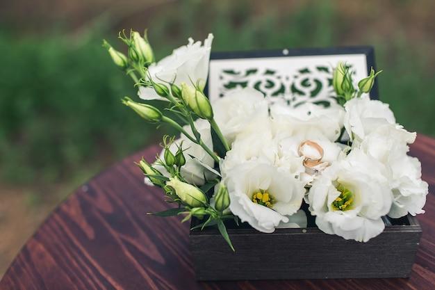 Trauringe liegen auf weißen eustomas in einer holzschatulle. hochzeitszeremonie konzept.
