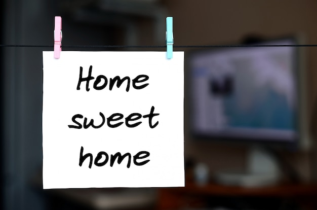 Trautes heim, glück allein. anmerkung wird auf einen weißen aufkleber geschrieben, der mit einer wäscheklammer an einem seil auf einem hintergrund des büroinnenraums hängt