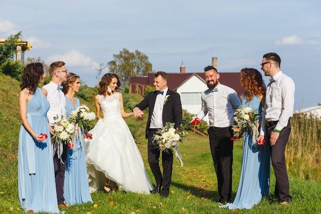 Trauzeugen und brautjungfern mit frisch verheirateten auf hochzeitszeremonie