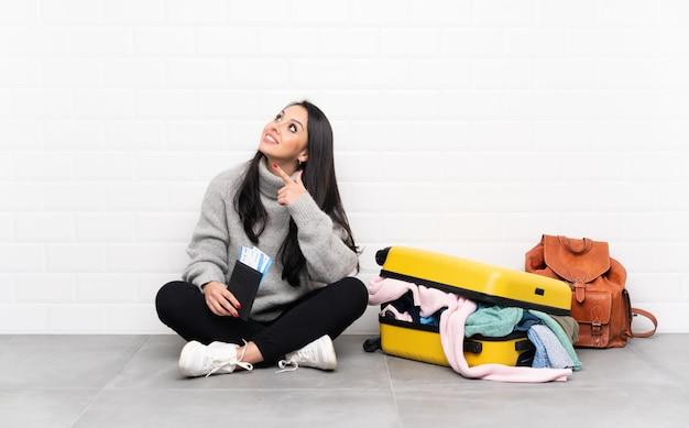 Traveller mädchen mit einem koffer voller kleidung auf dem boden sitzen mit dem zeigefinger eine tolle idee
