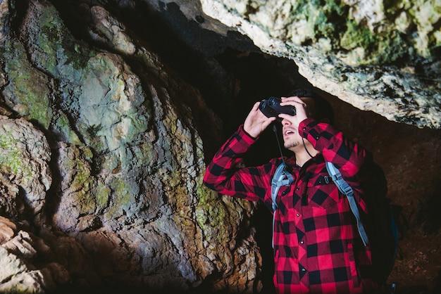 Traveller mit fernglas in der höhle