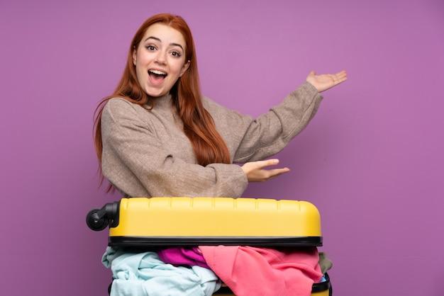 Traveller teenager-mädchen mit einem koffer voller kleidung, die hände zur seite streckt, um einzuladen, zu kommen