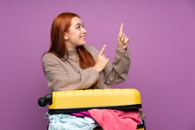 Traveller teenager-mädchen mit einem koffer voller kleidung zeigt mit dem zeigefinger eine tolle idee
