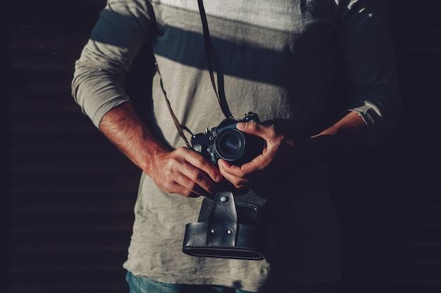 Tredny junger mann mit kamera in seinen händen