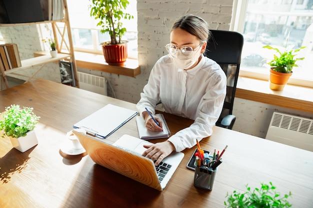Treffen. frau, die während der quarantäne von coronavirus oder covid-19 allein im büro arbeitet und gesichtsmaske trägt. junge geschäftsfrau, managerin, die aufgaben mit smartphone, laptop, tablet erledigt, hat online-konferenz.