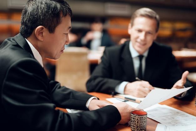 Treffen mit chinesischen geschäftsleuten in anzügen im restaurant