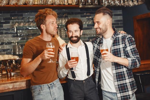 Treffen mit den besten freunden. drei glückliche junge männer in freizeitkleidung sprechen und trinken bier, während sie zusammen in der bar sitzen.