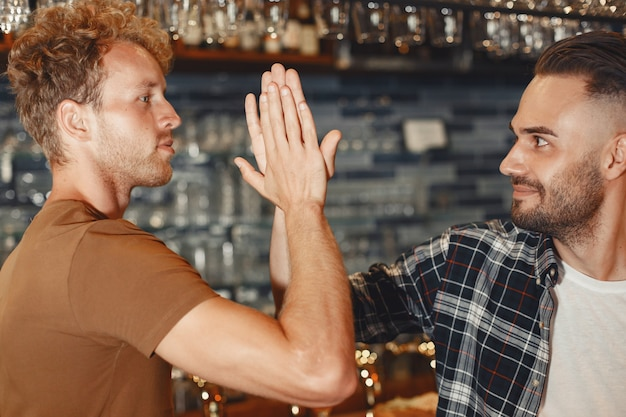 Treffen mit den besten freunden. zwei glückliche junge männer in freizeitkleidung sprechen und trinken bier, während sie zusammen in der bar sitzen.