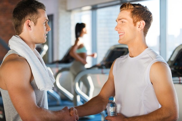 Treffen mit guten freunden im fitnessstudio. zwei hübsche junge männer, die sich die hände schütteln und lächeln, während sie in stehen