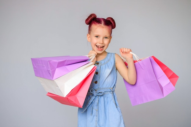 Treffen sie die rabatte. glückliches kleines baby lächelt mit papiereinkaufstüten.