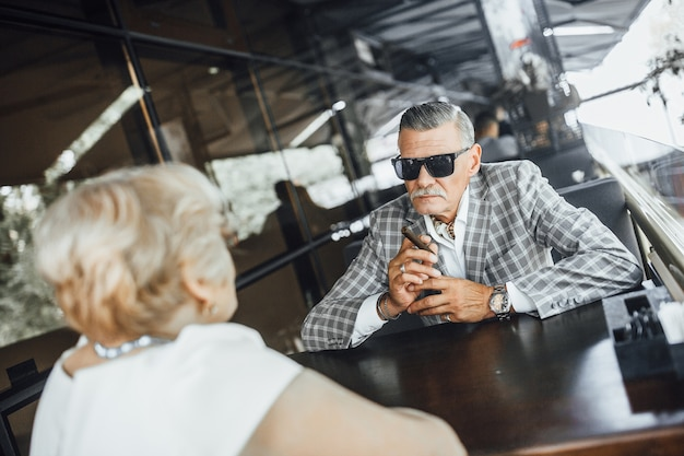 Treffen sie zwei seniorenpaare im modernen restaurant, mann raucht seine zigarette.