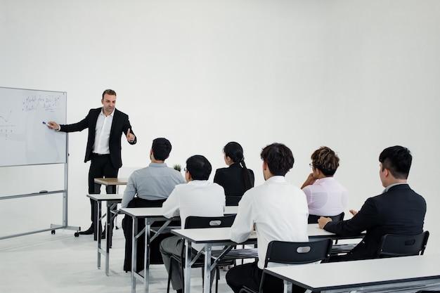 Treffen und planen der zusammenarbeit als team von asiaten und ausländern im weißen besprechungsraum.
