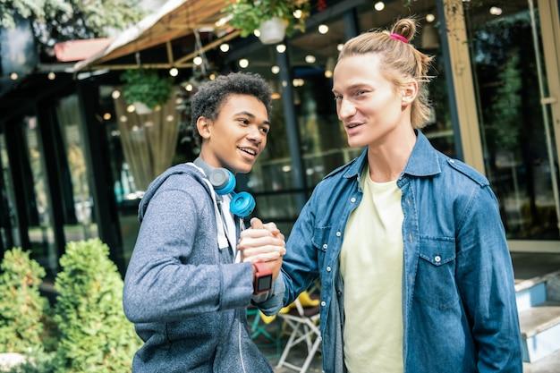 Treffen von freunden. erfreute junge männer, die zusammen auf der straße stehen und sich gegenseitig begrüßen