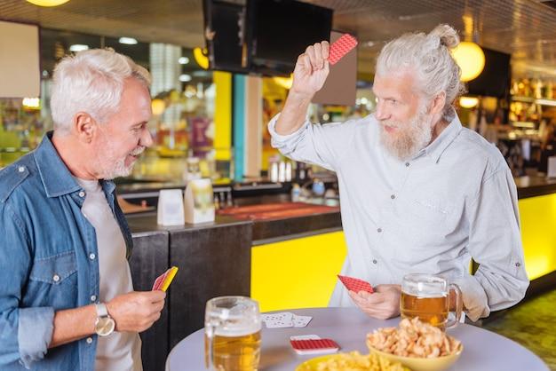 Treffen von freunden. freudige glückliche freunde, die am tisch stehen, während sie zusammen bier trinken