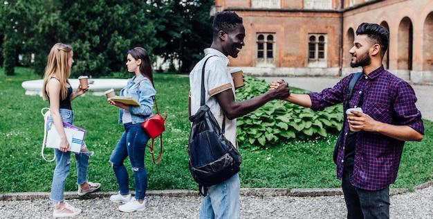 Treffen von studenten in der nähe der universität auf dem campus