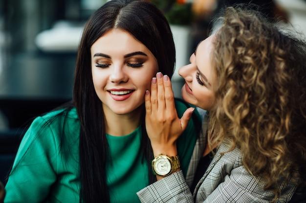 Treffen von zwei freundinnen, verbringen zeit zusammen im café, haben spaß beim essen von desserts, kuchen. gesagtes geheimnis für andere. glück.