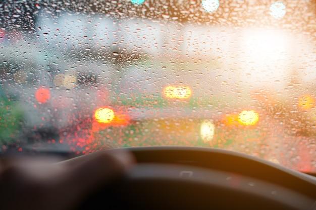 Treibendes auto und wassertropfen auf auto spiegel mit regen und stau auf der schnellstraße