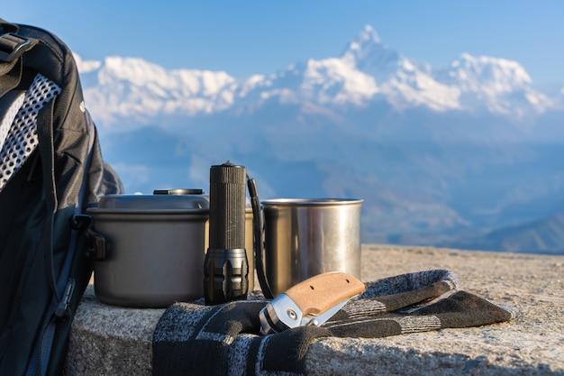 Trekking- oder wanderausrüstung mit annapurna-bergkette im hintergrund. rucksack, socken, metallbecher, wasserkocher, klappmesser und taschenlampe. konzept für outdoor-aktivitäten.