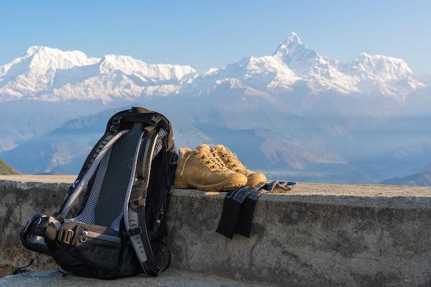 Trekking- oder wanderausrüstung mit annapurna-bergkette im hintergrund. rucksack, wanderschuhe und socken. konzept für outdoor-aktivitäten.