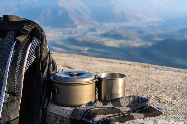 Trekking- oder wanderausrüstung. rucksack, socken, metallbecher und wasserkocher. konzept für outdoor-aktivitäten.