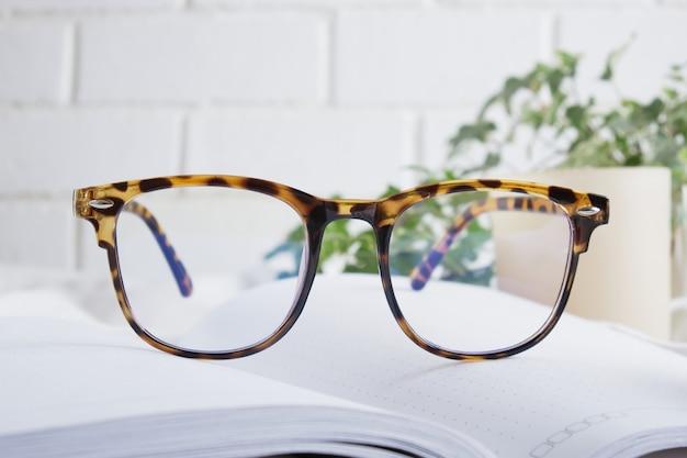 Trendige brille, duftkerze, eine blume in einem topf und ein offenes leeres notizbuch