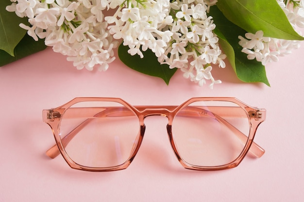 Trendige brillen und ein zweig aus weißem flieder auf rosa hintergrund, brillen und blumen, transparenter farbiger rahmen für brillen