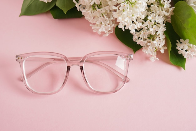 Trendige brillen und ein zweig aus weißem flieder auf rosa hintergrund, brillen und blumen, transparenter rahmen für brillen