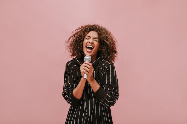 Trendige brünette dame in gestreifter, stylischer schwarzer kleidung, die mit geschlossenen augen singt und mikrofon an rosa wand hält..