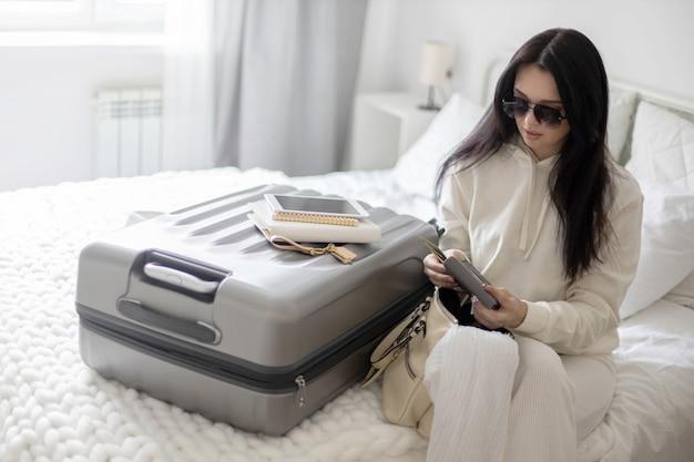 Trendige frau, die geld in der brieftasche überprüft, bevor sie das schlafzimmer reisefertig verlässt