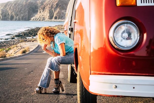 Trendige frau in reisetätigkeit setzt sich vor einem roten alten oldtimer-van, der an der küste geparkt ist