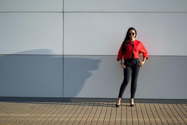 Trendige frühlingskollektion. junges attraktives mädchen in der modischen sonnenbrille, die stilvolle rote jacke und blaue hosen auf grauer wand trägt