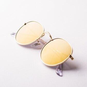 Trendige gelbe sonnenbrille mit goldenem rahmen mit glänzenden hellen reflexen