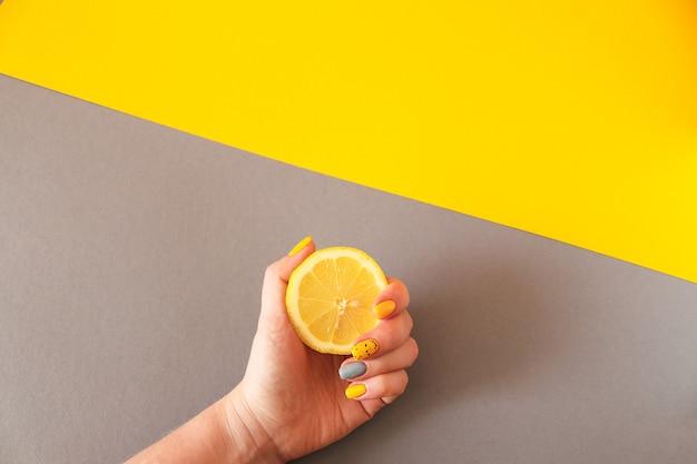 Trendige gelbe und graue frauenmaniküre weibliche hand, die ein zitronen-mode- und schönheitskonzept mit kopienraum hält