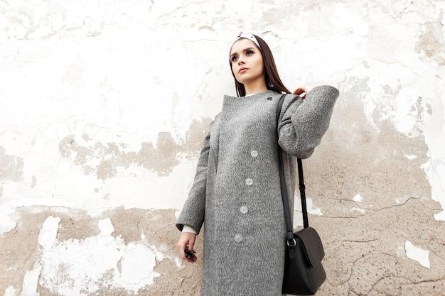 Trendige junge frau in modischem, lässigem jugendmantel mit schwarzer handtasche mit elegantem bandana ruht in der nähe der vintage-wand auf der straße. stilvolles urbanes mädchen-mode-modell posiert in der nähe des alten gebäudes in der stadt.