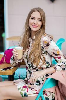 Trendige junge stilvolle frau, die im café sitzt