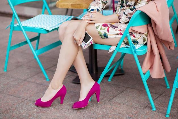 Trendige junge stilvolle schöne frau, die im stadtcafé in der straße sitzt